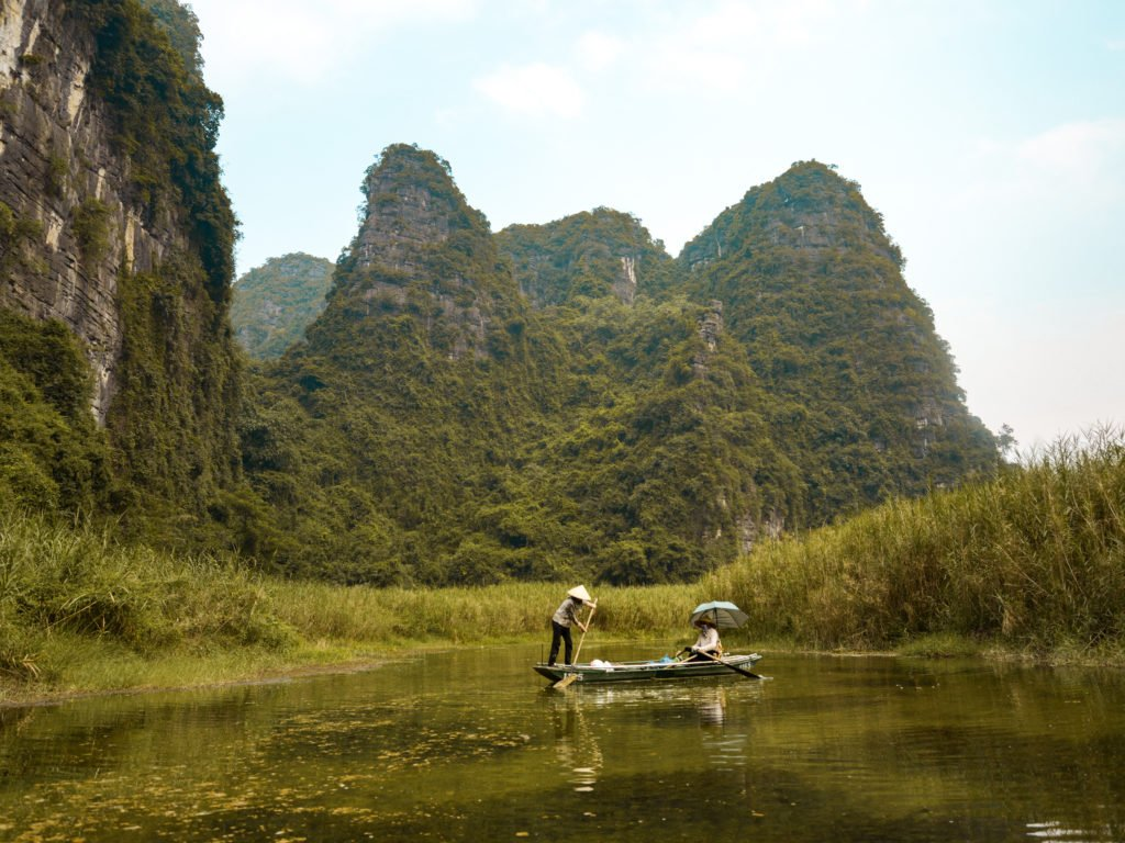 Visit Vietnam and experience its charm like these women in a boat in front of fields