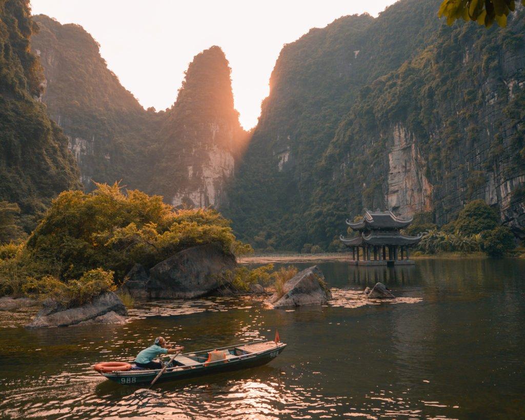 Lady rowing a boat at Trang An in Vietnam.