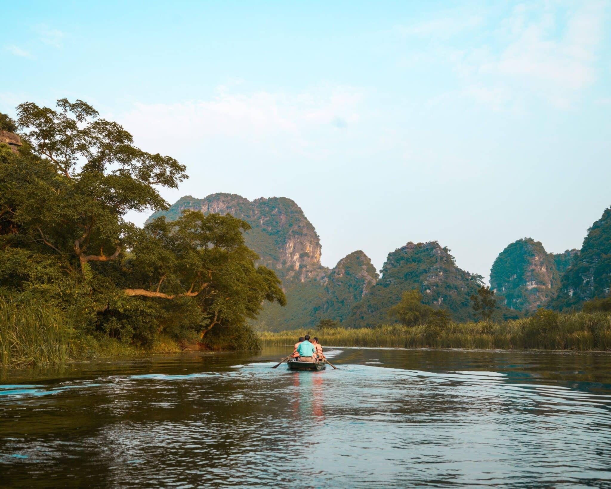 Explore Vietnam by boat; boat rowing through limestone formatinos