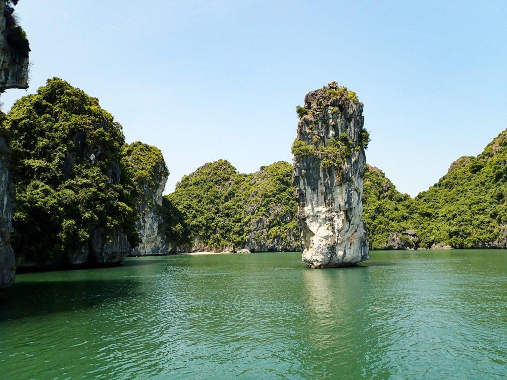 Limestone islands in Ha Long Bay surrounded by green water