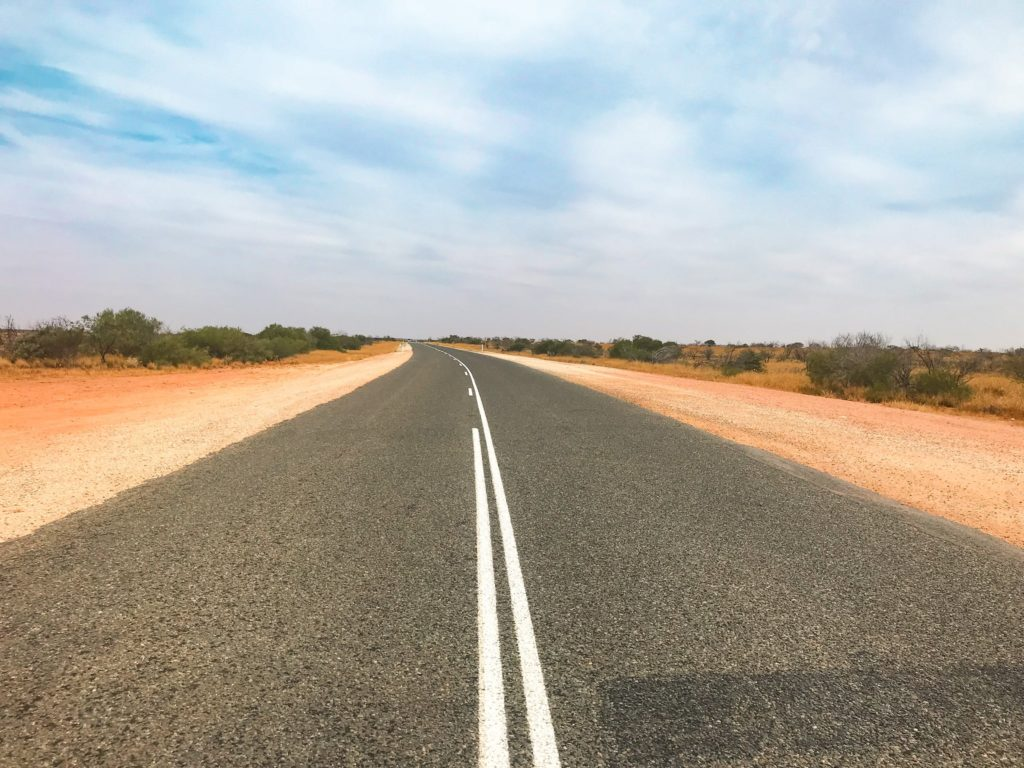 The open road in Australia with two lanes and red dirt at the side of the road.