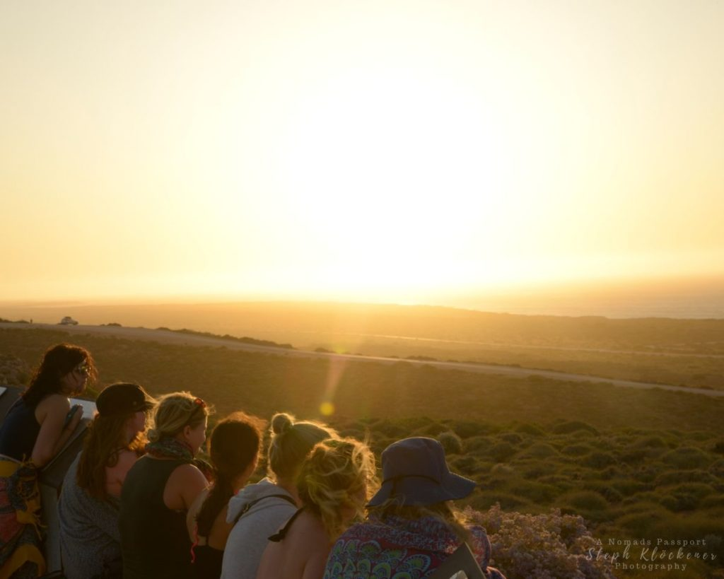 People watching the sunset over a hilly landscape and the ocean in Western Australia