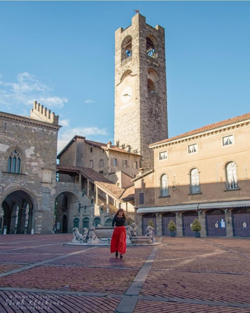 Woman waling across Piazza Vecchia in Bergamo which is the best short trip destination in Italy