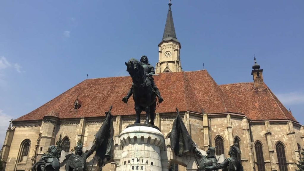 Statue and church in Cluj-Napoca which you can see during weekend getaways in the Balkans