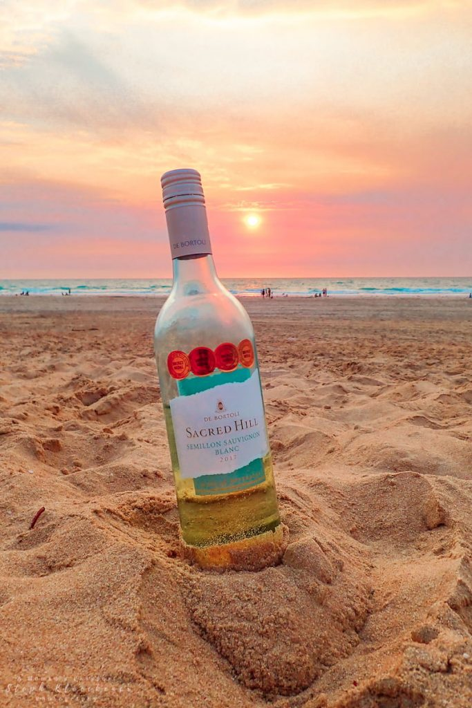 Australian wine bottle at the beach during sunset